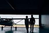 Fotografia vista posteriore delle siluette delle giovani coppie che camminano vicino aeroplano in hangar