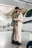 elegantní mladý pár v bundy všeobjímající poblíž letadla v hangáru