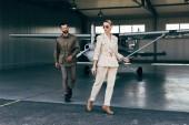Fotografie Módní pár v stylové bundy odstupující od hangáru s letadlo