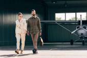 vážný muž, brašna a chůzi s elegantní přítelkyní nedaleko hangáru s letadlem