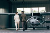 Fotografie rear view of man carrying bag and walking with stylish girlfriend near hangar with plane