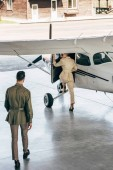 Photo high angle view of stylish man walking while his girlfriend boarding in plane