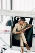 Fotografia giovane donna alla moda in occhiali da sole e rivestimento seduta in aereo