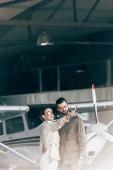 Fotografia bella giovane donna in occhiali da sole e giacca che punta di dito al ragazzo vicino aereo