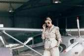 atraktivní mladá žena v sluneční brýle a sako pózuje u letadla