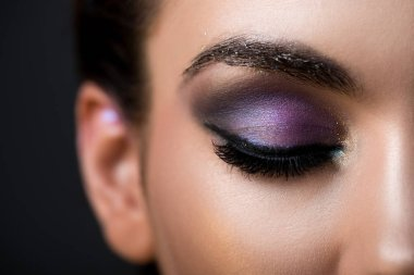 close up of girl with closed eye and glitter eyeshadows, isolated on grey