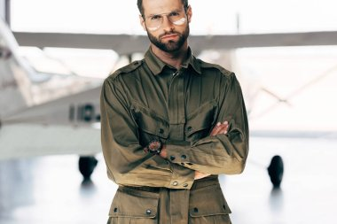 handsome young man in green jacket and eyeglasses standing with crossed arms near airplane
