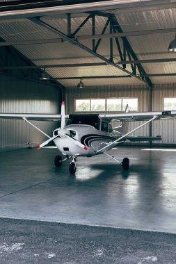 Small modern white airplane standing in hangar stock vector
