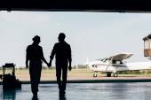 zadní pohled na siluety mladého páru, drželi se za ruce a procházky v hangáru u letadla
