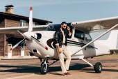 mladý muž pilot v kožené bundě a sluneční brýle představují poblíž roviny