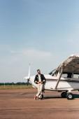Fotografia pilota alla moda maschile in giacca di pelle e occhiali da sole posa vicino aereo