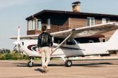 zadní pohled na stylové mužské pilot v kožené bundě, chůze v blízkosti letadlo