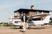 Fotografie Modische jungen männlichen Piloten in Lederjacke und eine Sonnenbrille, die zu Fuß in der Nähe von Flugzeug