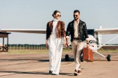 Fotografie happy young couple in leather jackets and sunglasses walking with retro suitcase near airplane