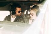 Fotografie mužské pilot sluchátka a brýle mluvit s přítelkyní v kabině letadla