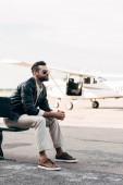 Fotografia elegante giovane pilota maschio in occhiali da sole che si siede sulla panchina vicino aereo