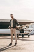 Photo serious male pilot in leather jacket and sunglasses posing near airplane