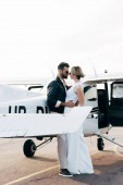Photo side view of stylish couple in sunglasses embracing each other near airplane