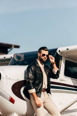confident male pilot in leather jacket and sunglasses posing near airplane