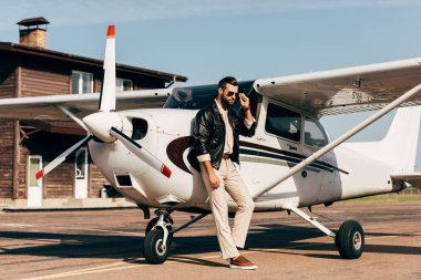young male pilot in leather jacket and sunglasses posing near plane
