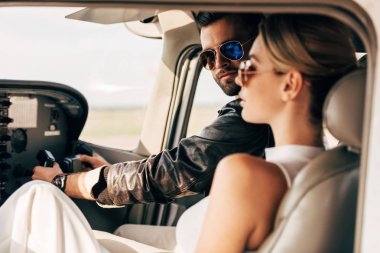 stylish male pilot in sunglasses and leather jacket looking at camera while his girlfriend sitting near in cabin of airplane