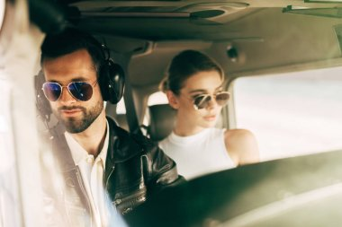 young male pilot in headset and sunglasses sitting with girlfriend in cabin of airplane