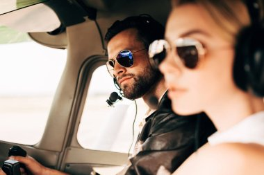 selective focus of handsome male pilot in headset and sunglasses sitting with girlfriend in cabin of airplane
