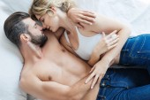 Fotografie top view of passionate young couple in love hugging and lying together on bed