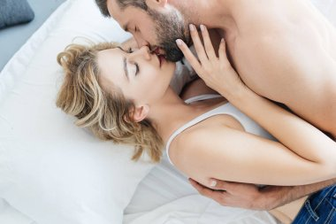 high angle view of beautiful seductive young couple kissing on bed