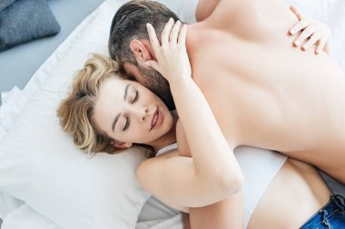 Top view of shirtless man hugging and kissing attractive girlfriend on bed stock vector
