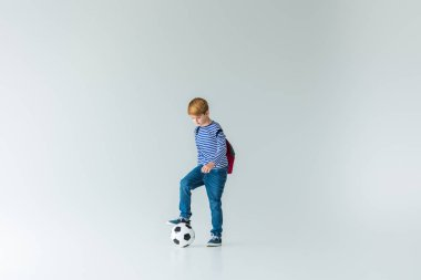 adorable schoolboy with backpack putting leg on fotball ball on white