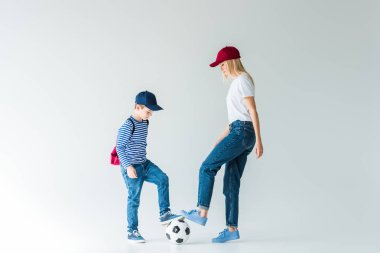 side view of mother and son in shirts and jeans playing football on white