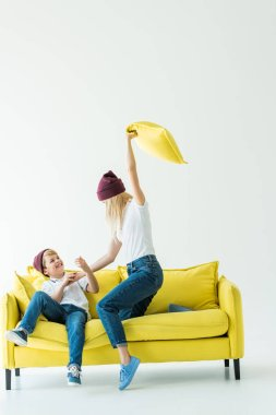 mother having fun and beating son with pillow on yellow sofa on white