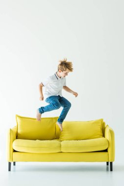 Adorable boy in casual clothes jumping on yellow sofa on white stock vector