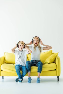 shocked mother and son listening music with headphones and touching heads on yellow sofa on white