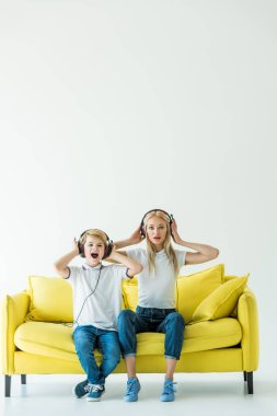 shocked mother and son listening music with headphones on yellow sofa on white