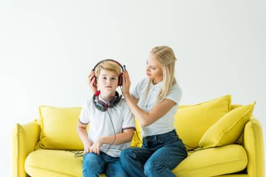 mother wearing headphones on son on yellow sofa isolated on white