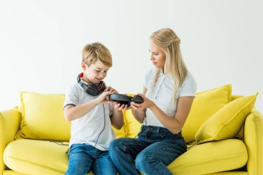 mother and son holding headphones on yellow sofa isolated on white