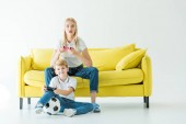 Fotografie excited mother and son playing video game on yellow sofa on white, football ball on floor