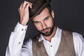portrét pohledný vousatý muž v stylovém klobouku, izolované Grey