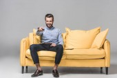 Photo cheerful businessman with remote control watching TV on yellow sofa on grey