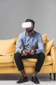Fotografie Mann Video-Spiel mit Joystick und Vr Kopfhörer auf gelben Sofa auf grau