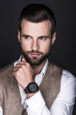 portrait of elegant bearded man with wristwatch, isolated on grey
