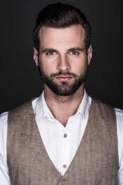 portrait of handsome serious bearded man in elegant trendy clothes, isolated on grey