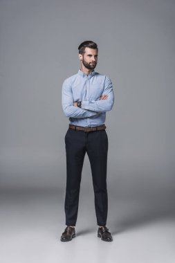 handsome confident businessman standing with crossed arms, on grey