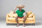 vidám ember, a mexikói sombrero néz foci mérkőzés labdát a szürke sárga kanapén ülve