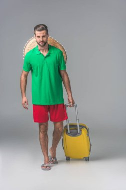 traveler with mexican sombrero walking with yellow baggage on grey