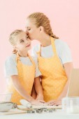 mother kissing her daughter while preparing dough isolated on pink
