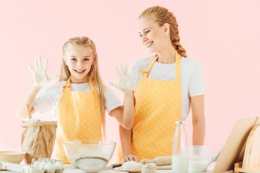 Happy mother and daughter in yellow aprons cooking together isolated on pink stock vector