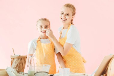 Smiling mother and daughter with flour on faces looking at camera while cooking isolated on pink stock vector
